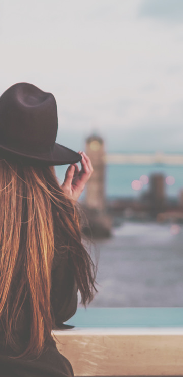 Photo of woman standing in front of Tower Bridge in London holding her hat